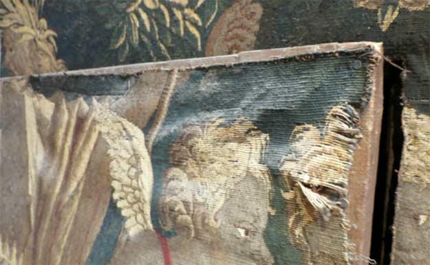 Détail de la découpe sur une des porte : clouage, affaissement de la tapisserie, usures des trames et chaines coupées.