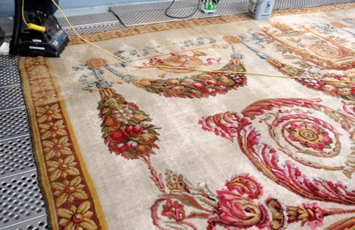 Nettoyage d'un très grand tapis, tissé en 1810 au point de Savonnerie pour le troisième salon de l'impératrice à Compiègne