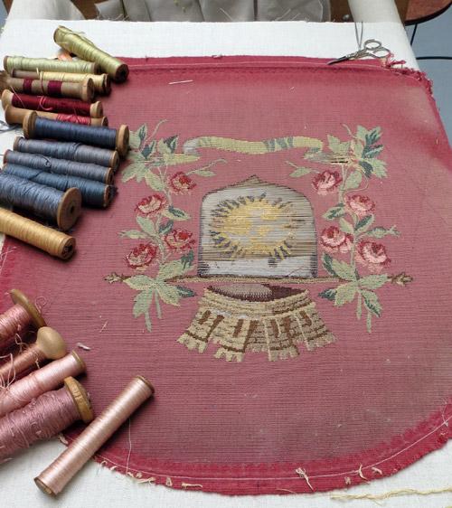 La tapisserie du dossier d'un siège tendue sur une toile pour être restaurée.